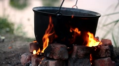 Cooking on a fire in the campaign - stock footage