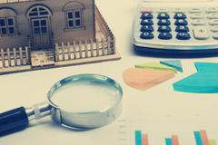Model house, construction plan for house building, magnifying glass compass - stock photo