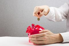 Savings Woman Putting Coin In Piggy Bank. Savings, finances, economy and home Stock Photos