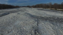 Aerial view of ice on partially frozen river as camera moves close to surface Stock Footage