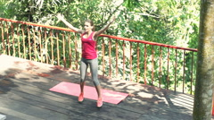 Young woman exercising, doing jumping jacks on terrace Stock Footage