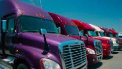 Slow pan up of purple freight liner truck parked in an outdoor lot Stock Footage