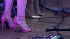 Feet tattooed and shod with pink shoes are on on scene of a singers Stock Footage