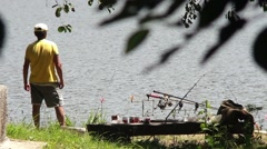 Fisherman who sits on the lakeshore and check all the time if any cork goes Stock Footage