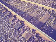 Retro filtered photo of railway tracks with wooden sleepers Stock Photos