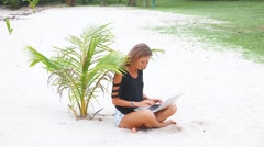 Blond girl with a laptop on tropical beach, freelance concept - stock footage