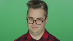 Young man with glasses starts laughing, on a green screen background Stock Footage