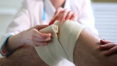 Female doctor puts a tight bandage on the injured knee of the patient. Stock Footage