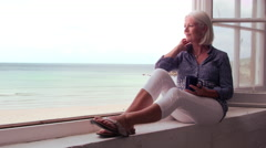 Woman Sits At Window And Looking At Beach View Shot On R3D Stock Footage