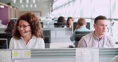 Male and female call centre workers wearing headsets Stock Footage