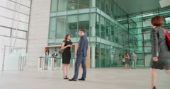 Business people passing couple in foyer of a modern building Stock Footage
