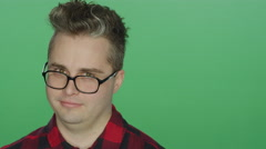 Young man with glasses nodding his head, on a green screen background Stock Footage