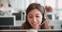 Young woman working in a call centre using a headset - stock footage