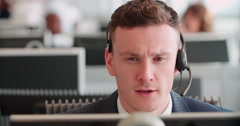 Young man working in a call centre using a headset - stock footage