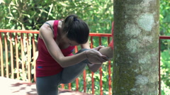 Young woman warming up, stretching leg on terrace Stock Footage