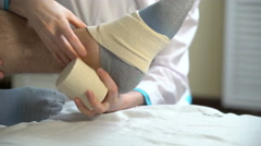 Female doctor puts a tight bandage on the injured ankle of the patient. 4k - stock footage