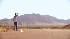 Woman Hitchhiking Along Road Using Mobile Phone Shot On R3D Stock Footage