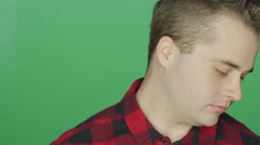 Young man staring ahead sadly, on a green screen background Stock Footage