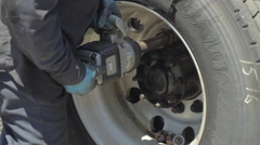 Auto mechanic removing nuts from concave freight liner truck tire - stock footage