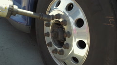 Auto mechanic removing nuts from convex freight liner truck tire Stock Footage