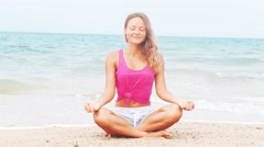Woman doing meditation near the ocean beach. Yoga silhouette Stock Footage