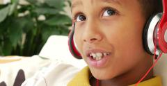 Brazilian child listening to music with a headsets Stock Footage