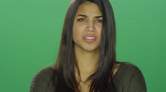 Young woman looking angry, on a green screen studio background - stock footage