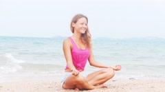 Woman doing meditation near the ocean beach. Yoga silhouette - stock footage