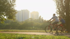 Happy married couples and family with kids go cycling together on hot summer day Stock Footage