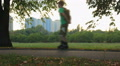 Teenager rollerblading, parents with children riding bicycles in summer park Footage