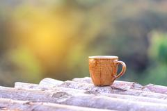 Coffee cup on wooden coaster natural background on the morning. Stock Photos