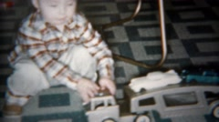 1962: Toddler boy playing with car carrier truck on kitchen floor. Stock Footage