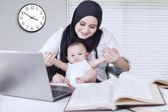 Mother Playing with Baby while Working Stock Photos