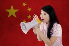 Woman congratulate Chinese new year with megaphone - stock photo