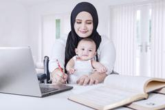 Woman with her Baby Working from Home - stock photo