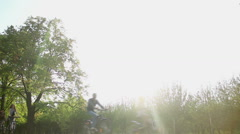 Happy adults and children go bike riding, enjoying fresh air in green city park Stock Footage