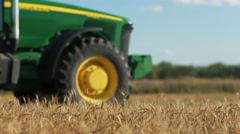 Waving Wheat in front of a Tractor Stock Footage
