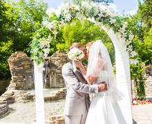 First kiss of newly married couple under wedding arch - stock photo