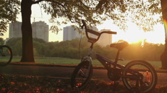 Children's bike left in park standing in sunset rays, happy childhood memories Stock Footage
