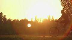 Energetic young men cycling in the park at sunset, living active healthy life Stock Footage