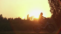 Young man and woman hired bikes for a ride in beautiful summer park at sunset Stock Footage
