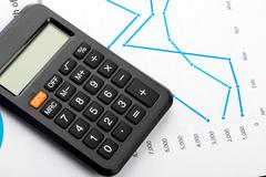 Financial graphs and charts analysis with calculator Stock Photos