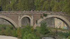 People walking and standing on Ponte Fabricio over Tiber river in Rome Stock Footage