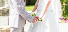 Bride and groom holding hands outdoors Stock Photos