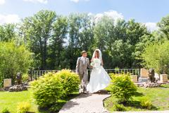 Bride and groom holding hands outdoors - stock photo