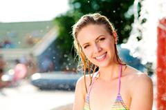 Woman in bikini sunbathing in aquapark. Summer heat and water - stock photo