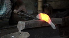 Close up of hammering red hot sickle by an Indian blacksmith. Stock Footage