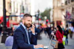 Manager with laptop and smart phone, sunny Piccadilly Circus, Lo - stock photo