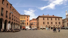 People walk by the square (Piazza Grande) in Modena, Italy. Stock Footage