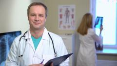 A nurse shows a male doctor x-ray. Doctor smiling at the camera. 4k - stock footage